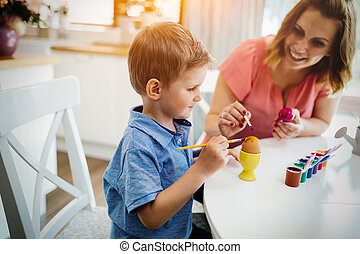 Mother and her son having fun decorate eggs