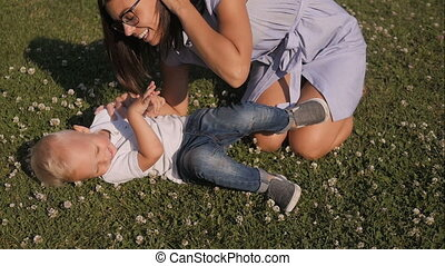 Mother And her Son Having Fun On Grass In Park. Mom Tickling And Kissing Son