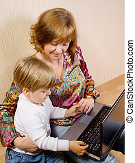 Mother and her son siting on a floor with the laptop