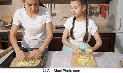 Mother and her teen daughter are cooking apple pie...