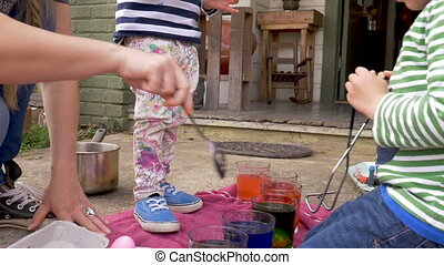 Mother and her two children dyeing easter eggs together outside