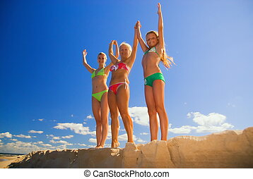 Mother and her two daughters stands on a beach with their hands up