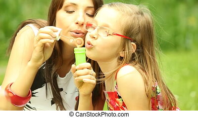 Mother and kid blowing soap bubbles