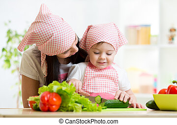 Mother and kid daughter knife cut cucumber - Mother and kid...