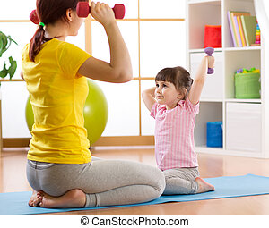 Mother and kid daughter training with dumbbells in home room