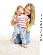 Mother and Kid Girl, Happy Mom with Baby Daughter, Infant Child one year old and Young Mum on White carpet