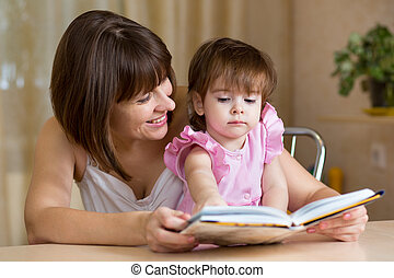 mother and kid girl read a book