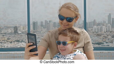 Mother and kid on hotel rooftop taking selfie with cell. Tel...