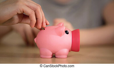 Mother and kid putting money in piggy bank, mom telling about family budget