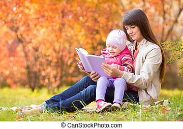 mother and kid read a book outdoors in autumn