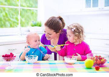 Mother and kids having breakfast