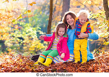 Mother and kids in autumn park - Mother and kids play in...