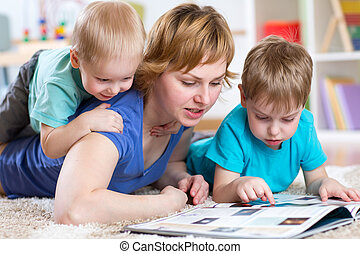 Mother and kids reading book at home