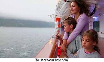 Mother and kids stand on ship deck which sail near coastline