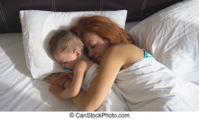 mother and little boy awake in the morning in hotel