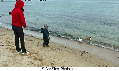 Mother and little boy feeding ducks