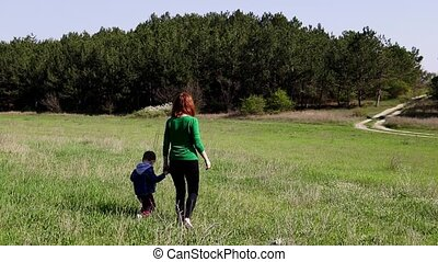 mother and little boy go on the field