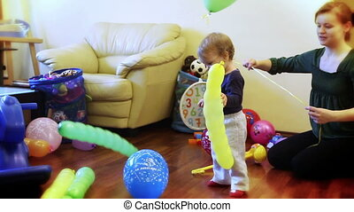 Mother and little boy playing with balloons