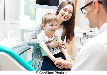 Mother and little boy talking to dentist in dental clinic -...