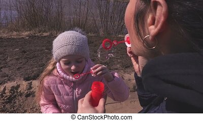 Mother and little daughter blowing up soap bubbles in the park