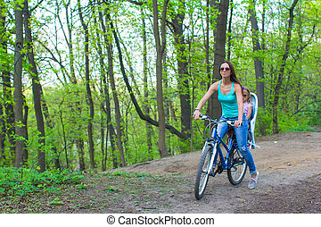 Mother and little daughter cycling bicycle at the park