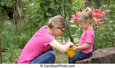 Mother and little daughter eat berries mulberry