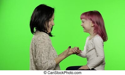 Mother and little daughter playing rock paper scissors. Chroma Key. Leisure game