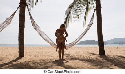 mother and little daughter roll in hammock across palm trees