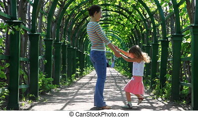 Mother and little daughter rotate holding hands in arched corridor braided plants