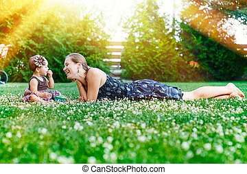 Mother and little daughter sit on the grass in a park at a picnic