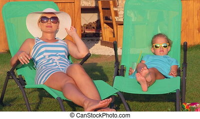 Mother and little daughter with drink sitting on sun loungers in backyard