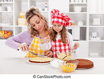 Mother and little girl making a cake together