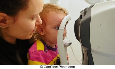 Mother and little girl - optometrist checks Child's Eye -...