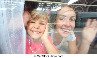 mother and little girl smiling and waving from the train...