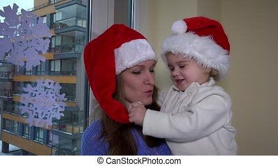 mother and little girl with red santa hat have fun near window. Snow flakes