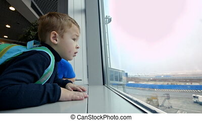 Mother and little son looking out the window at airport