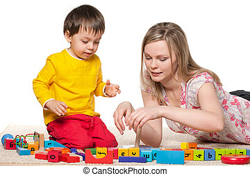 Mother and little son play with blocks