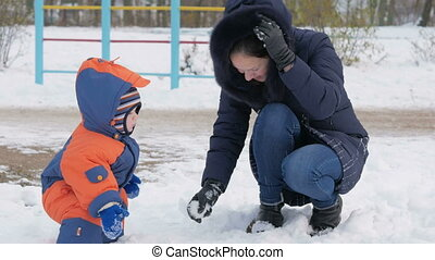 Mother and little toddler boy walking in the winter playground and having fun with snow. Family enjoying winter. Winter lifestyle concept.