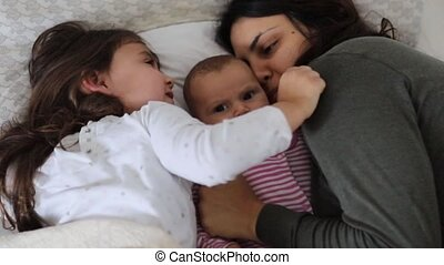 FHD Video of a woman lying down on a bed while kisses and hugs her two young daughters