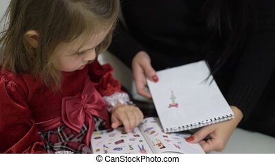 Mother and small daughter watching books with stickers -...