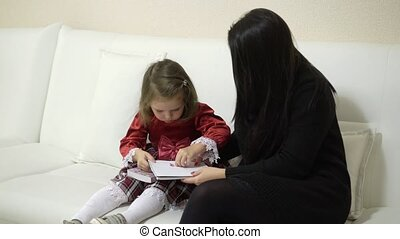 Mother and small daughter watching books with stickers