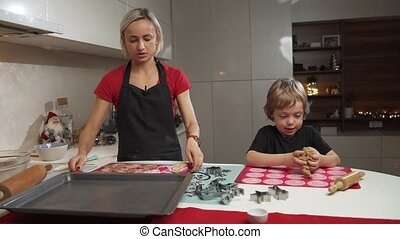 Mother and small son getting ready for christmas, baking gignger cookies together