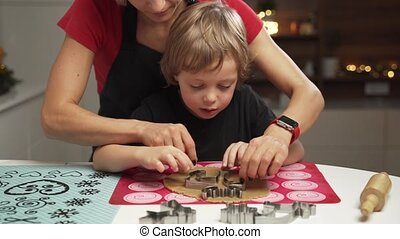 Mother and small son getting ready for christmas, baking...