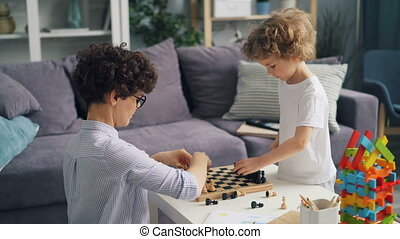 Mother and small son placing chess pieces on chessboard...