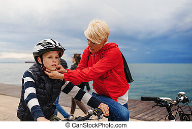 Mother and small son with bicycles outdoors standing on beach.