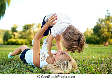 Mother and son are playing hugging on the grass in the park.