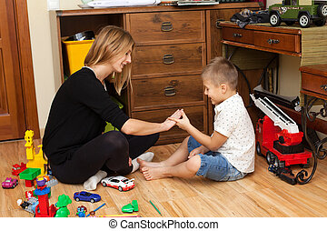 Mother and son are playing in the playroom