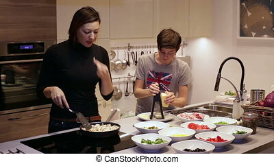 Mother and son are preparing dinner in the kitchen
