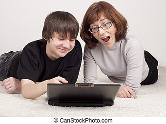 mother and son are together, work with computer - mother and...