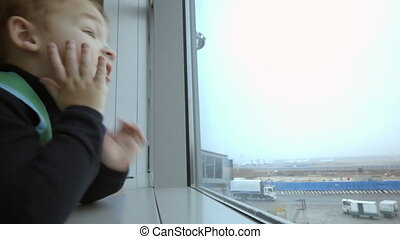 Mother and son at airport spending time looking out the window